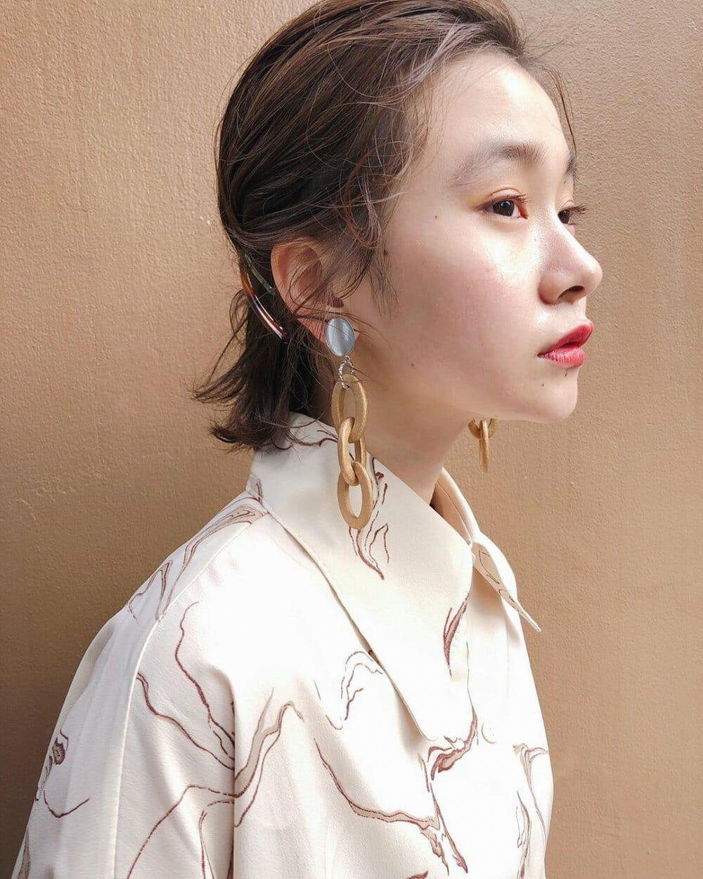 ミニボブヘアスタイルの髪型をオールバック前髪にヘアアレンジしている女性