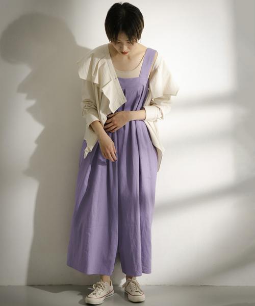パープルのサロペットにオフホワイトのフリルカラーシャツを羽織った女性