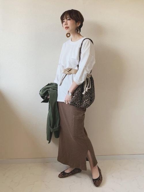 白のビッグトップスにブラウンのタイトスカートを合わせた女性