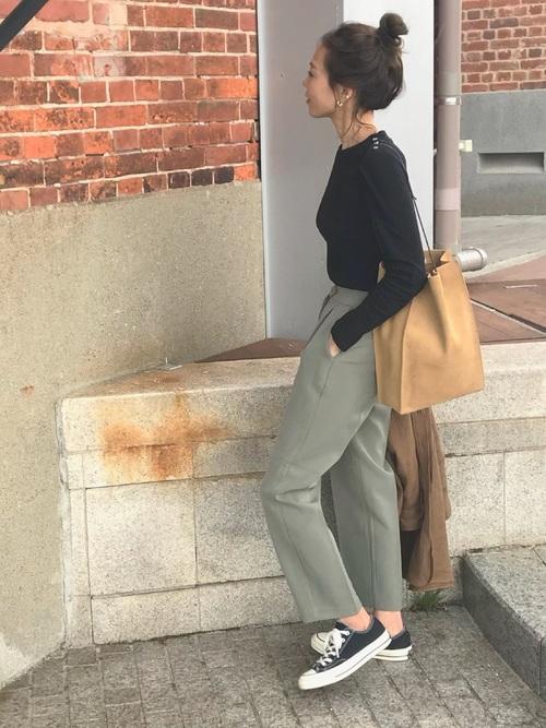 黒のTシャツにカーキのパンツを合わせた女性