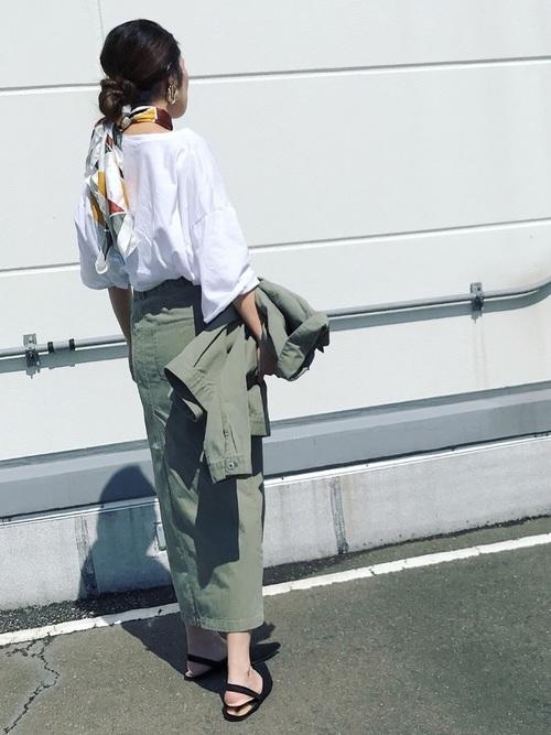 白Tにカーキのデニムスカートを合わせて、首にスカーフを巻いた女性