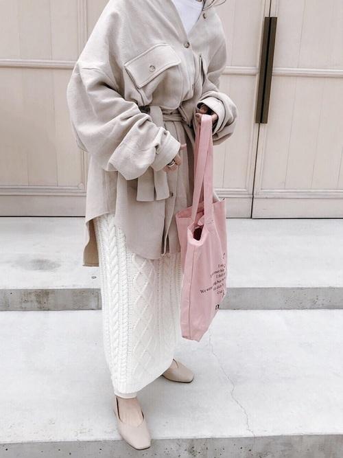 ワントーンコーデにピンクバッグの女性