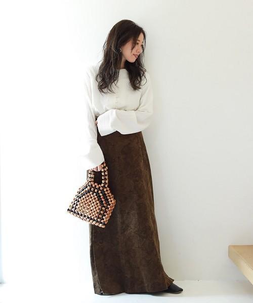 白のブラウスにブラウンのペイズリー柄のスカートを合わせて、ウッドビーズのバッグを持った女性