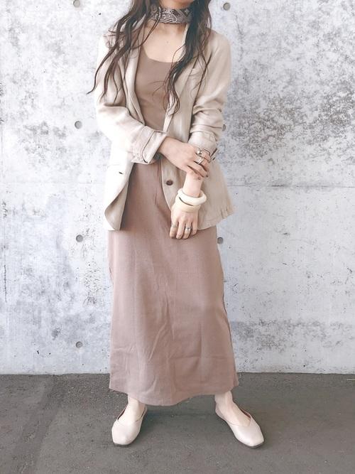 ベージュのタンクトップとタイトスカートにベージュのジャケットを羽織り、首にブラウンのスカーフを巻いた女性