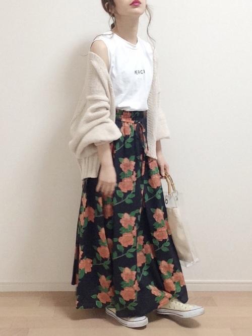 ガウンを羽織り白トップスに大きい花柄のマキシスカートにコンバースを履く女性