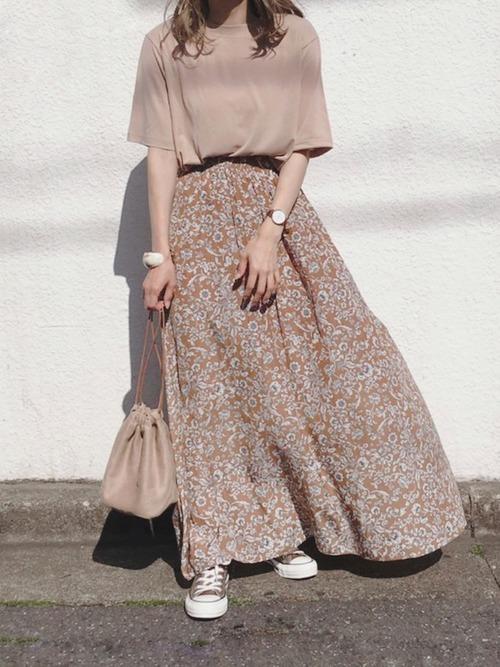 ベージュのTシャツにベージュの小花柄スカートにベージュのコンバースの女性
