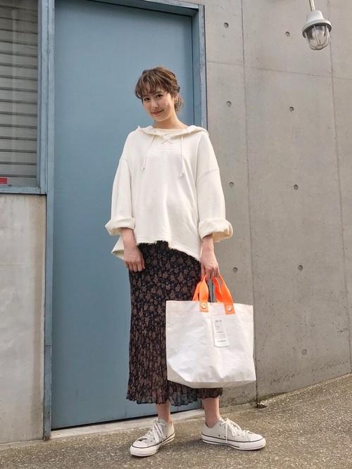 白トップスにプリーツの小花柄スカートにホワイトのコンバースに大き目バッグを持つ女性
