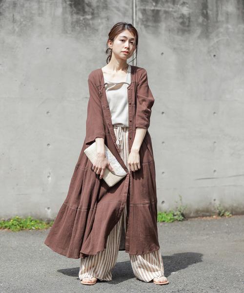 ベージュのタンクトップとストライプパンツに、ブラウンのティアードワンピを羽織った女性