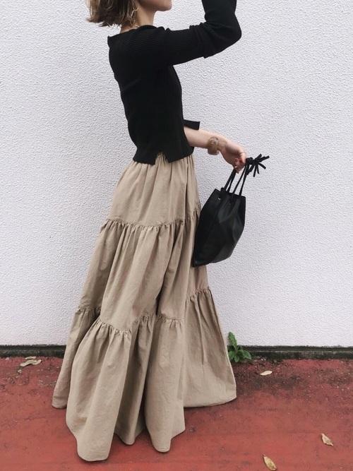 黒のトップスにベージュのティアードスカートを合わせた女性