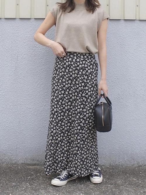 ベージュのカットソーにブラックの花柄のスカートにコンバースを履く女性