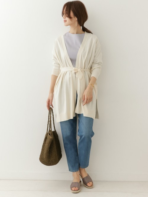 パープルのTシャツにデニムを合わせて、ホワイトのベルト付きカーディガンを羽織った女性