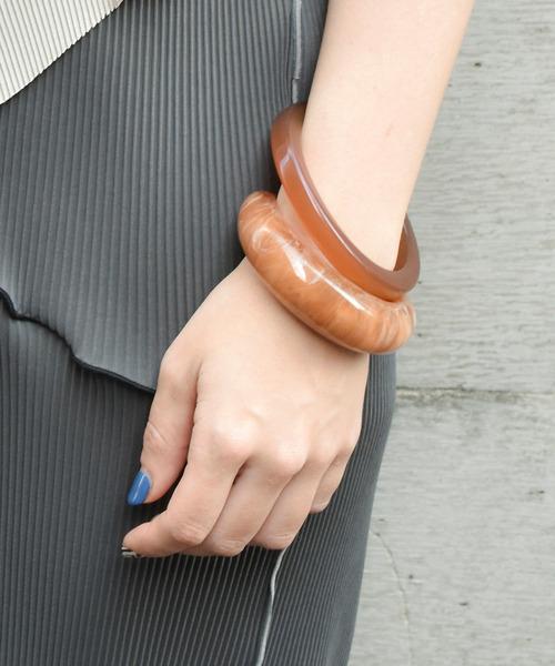 スクエアカットバングル色違い二本を腕に着けている女性の手元アップ画像