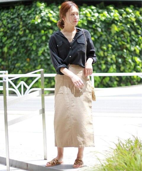 黒シャツにベージュスカートとフラットサンダルを合わせたレディースコーディネート