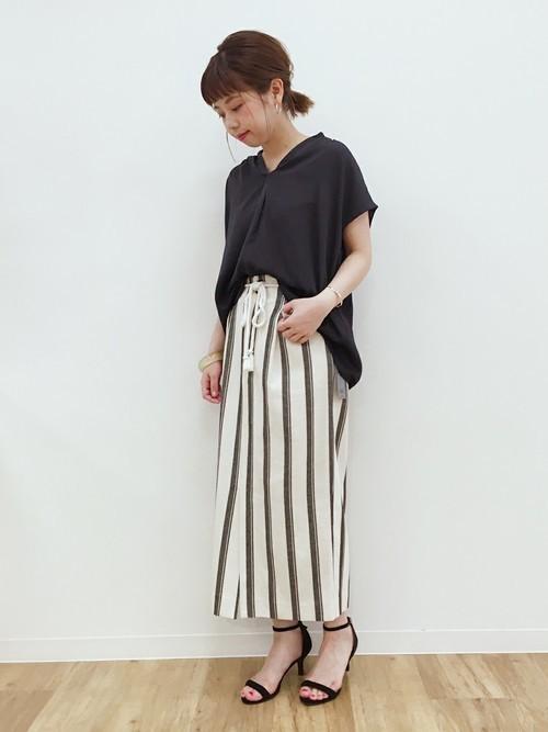 黒い半そでトップスにモノトーンのリボン付きスカートにミュールを履く女性