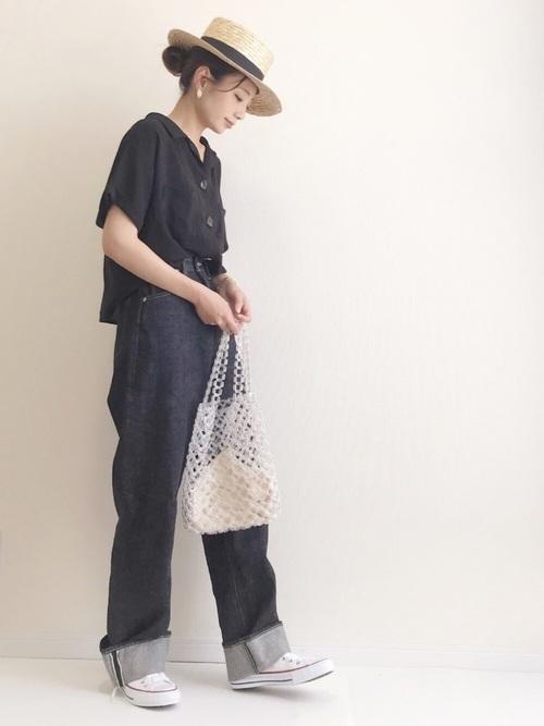 黒の開襟シャツにデニムを合わせて、カンカン帽をかぶった女性