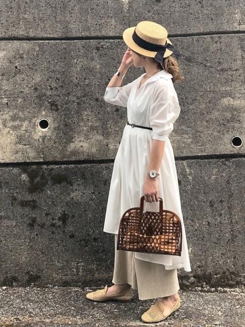 白のシャツワンピースにベージュのリブパンツを合わせて、カンカン帽をかぶった女性
