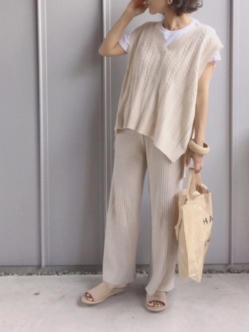 ベージュのニットベストにTシャツにリブパンツを履いてバングルを付ける女性