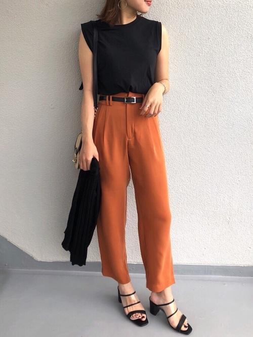 黒いノースリーブトップスにテーパードのオレンジパンツにサンダルを履く女性
