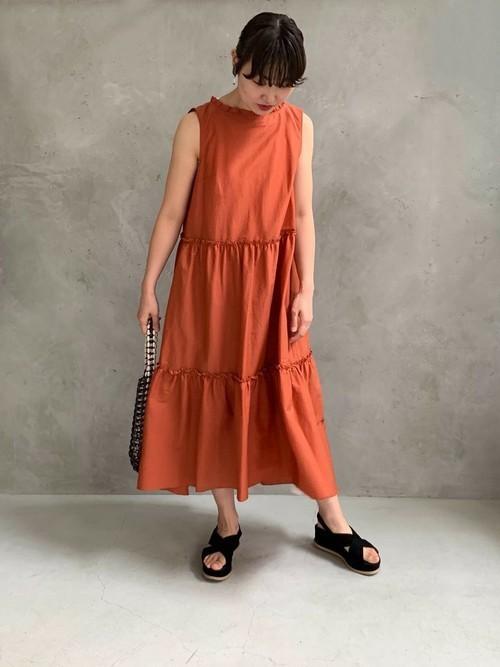 オレンジのノースリーブワンピースに黒いサンダルを履いてポーズをとる女性