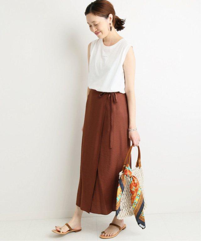 白のノースリーブのチビロゴTシャツにブラウンのラップスカートを合わせた女性