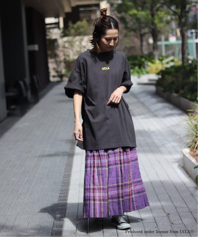 黒のビッグシルエットのチビロゴTシャツにパープルのチェック柄スカートを合わせた女性