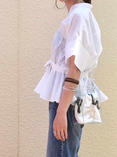 白チュニックにデニムにバングルを付けてクリアのショルダーバッグをかける女性