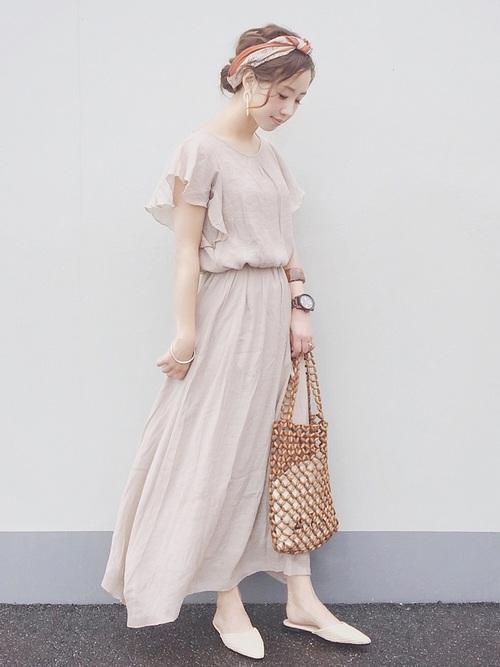 ベージュのフリルスリーブワンピースを着た女性