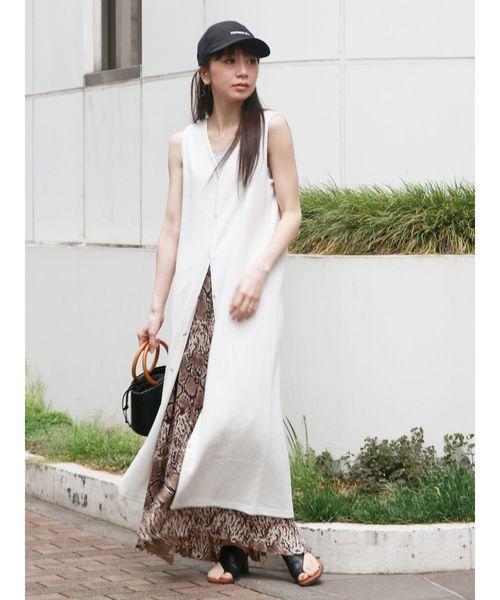 白のノースリワンピースにベージュのパイソン柄のプリーツスカートをレイヤードした女性