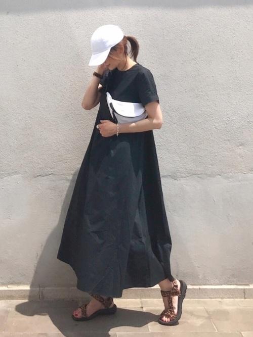 黒のTシャツワンピと白キャップコーデの女性