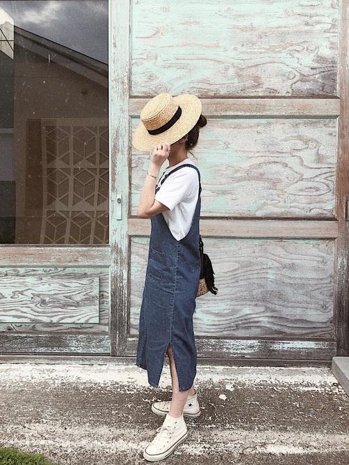 デニムのジャンバースカートを履く女性