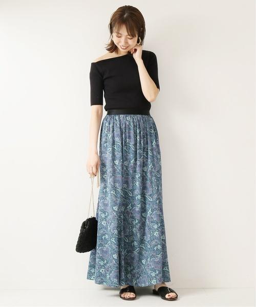黒のワンショルダートップスにブルーのペイズリー柄スカートを合わせた女性