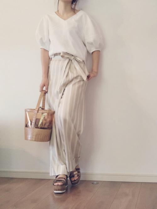 白のブラウスにベージュのストライプ柄ラップパンツにサンダルを履く女性