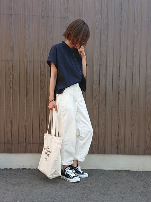 ネイビーのシャツに白のベイカーパンツを合わせた女性