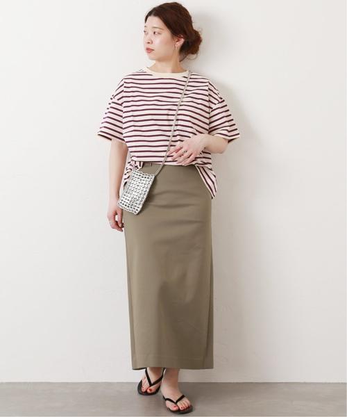 パープルのボーダーTシャツにベージュのタイトスカートを合わせた女性