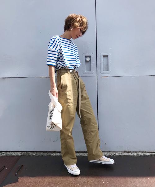 ブルーのボーダーTシャツにカーキのパンツを合わせた女性