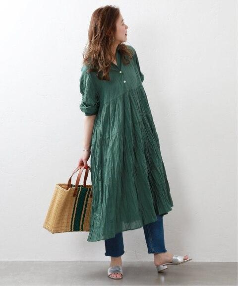 パーソナルカラーがイエベスプリングの色黒女性に似合う色のグリーンワンピースを着た画像