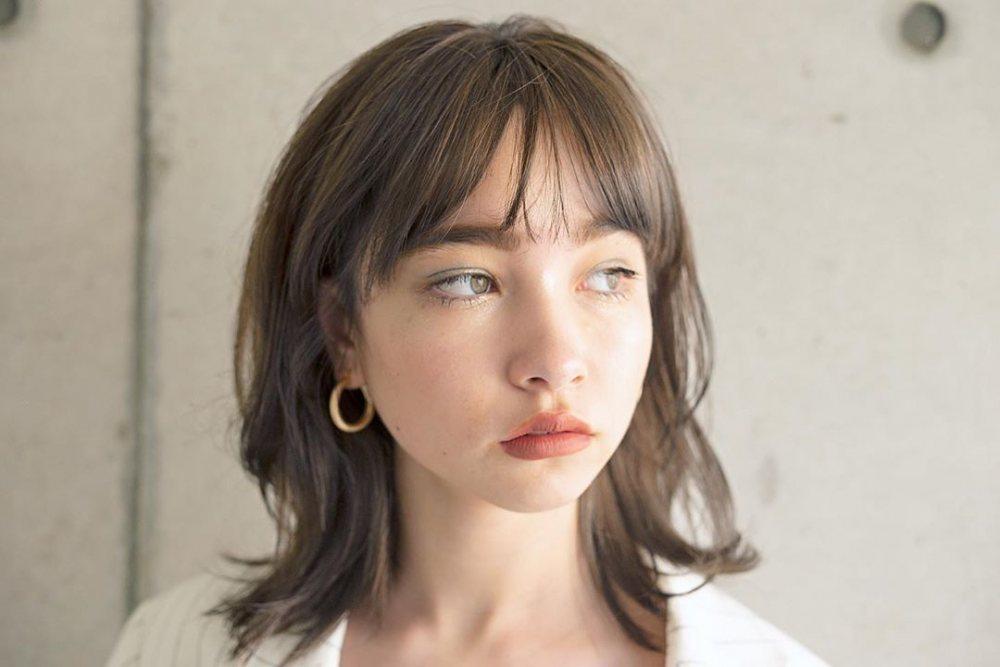 猫っぽいと言われる特徴でハイライトでツヤメイクをしたミディアムヘアスタイルの猫顔女性