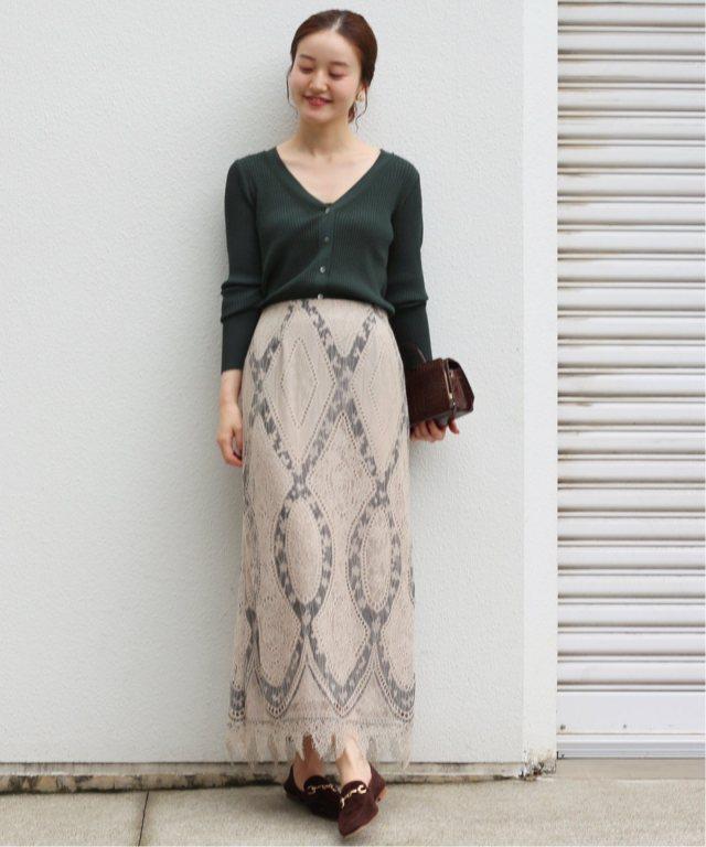 深緑色のリブカーディガンに似合う色のベージュロングスカートを着たレディース秋冬コーディネート