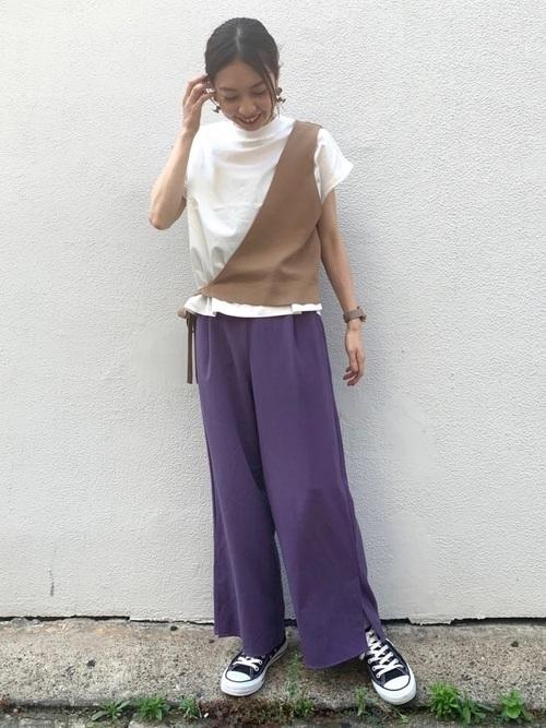 白いTシャツにブラウンのワンショルベストにパープルのワイドパンツを履く女性
