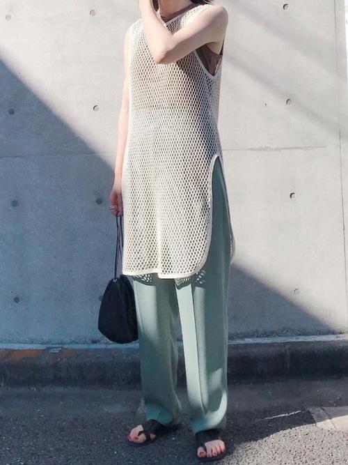 メッシュタンクをレイヤードしてくすみグリーンのテーパードパンツを履く女性