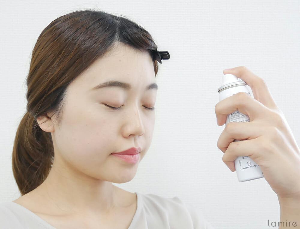 ミスト化粧水を顔全体に吹きかけている女性の写真