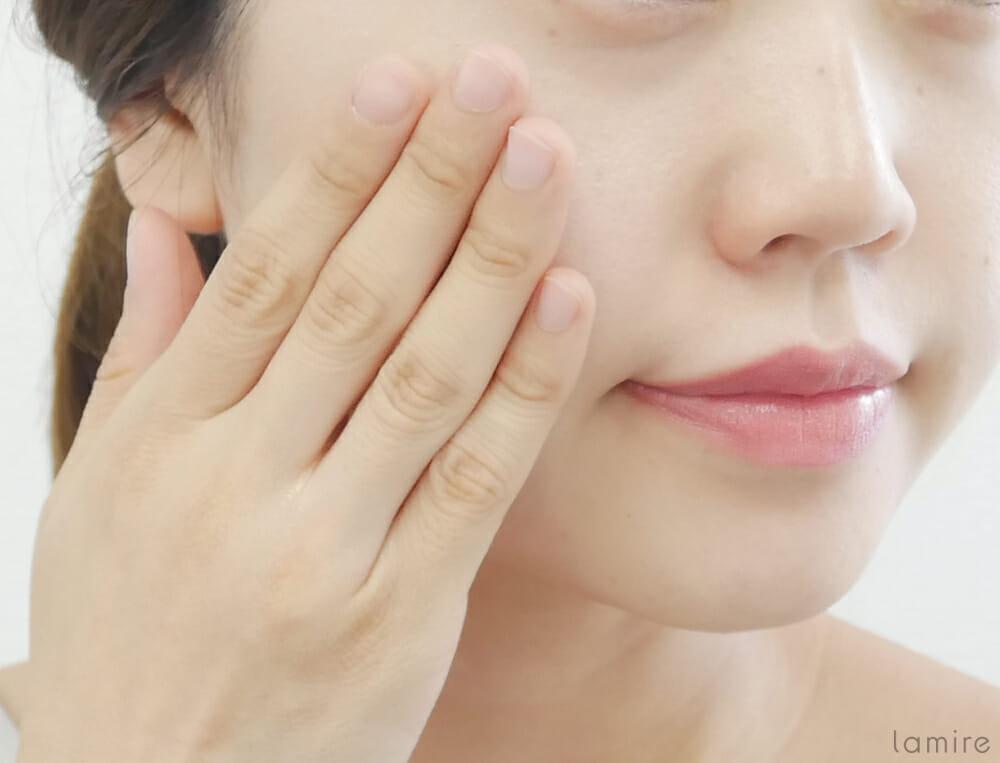 手を使って化粧水を肌に付けている女性の写真