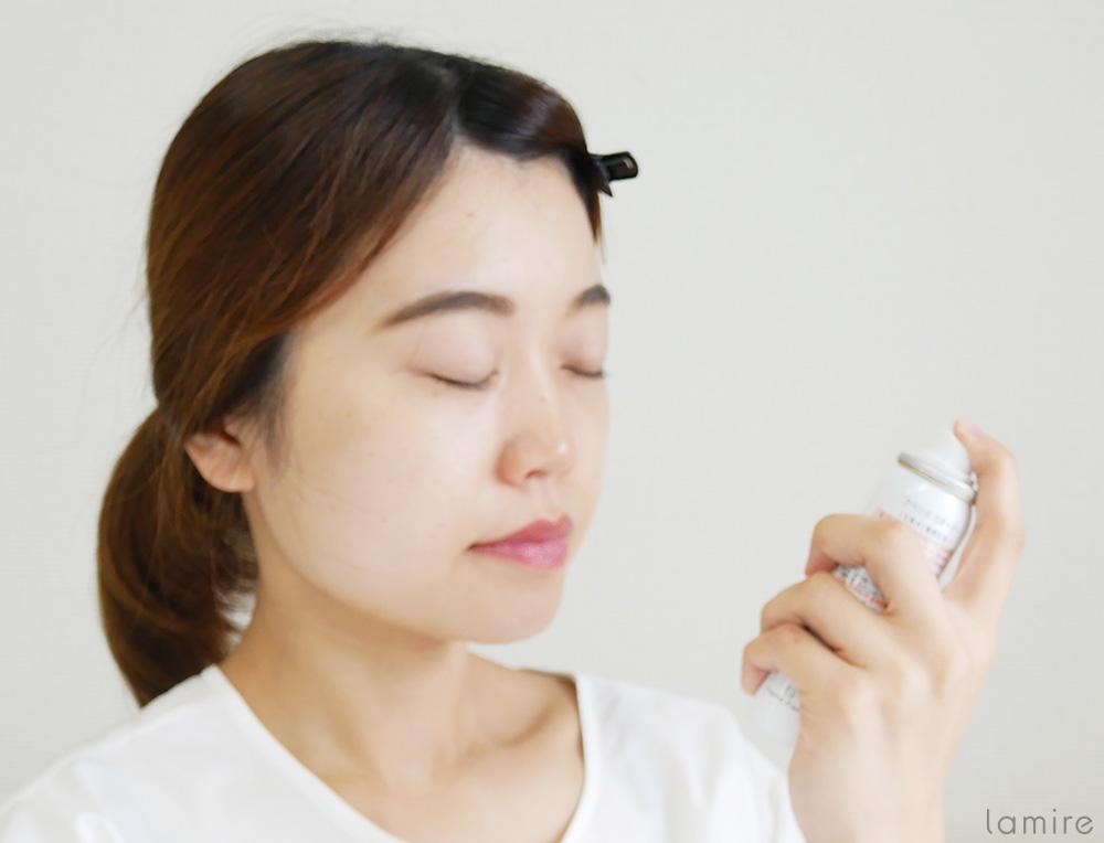 蒸しタオルを外した後、化粧水で顔を保湿している女性の写真
