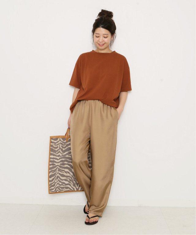 ベイクドメープルのTシャツにキャメルのパンツを合わせた女性