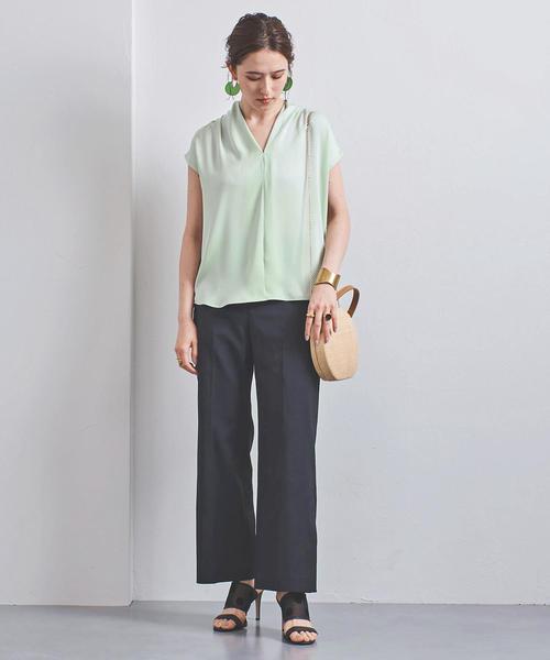 グリーンのブラウスにネイビーパンツを合わせた大人女性の春夏の同窓会にぴったりな服装