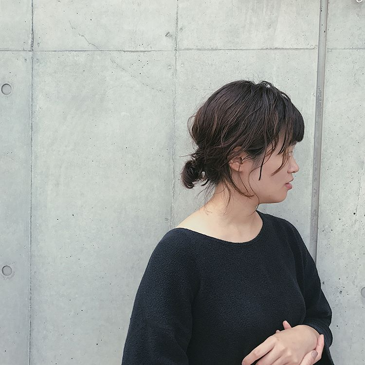 前髪ありのボブヘアスタイルを後れ毛を出したひとつ結びヘアアレンジにしている女性