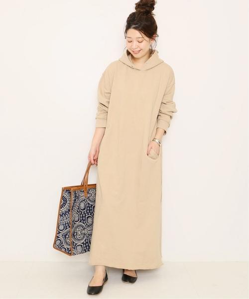 ベージュのフードワンピを着る女性