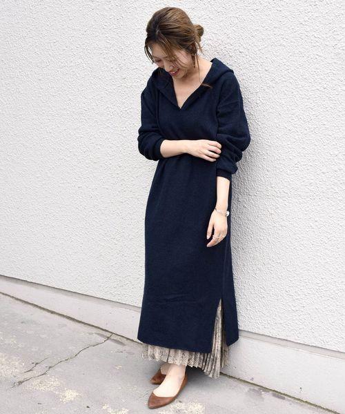 フード付きニットワンピを着る女性