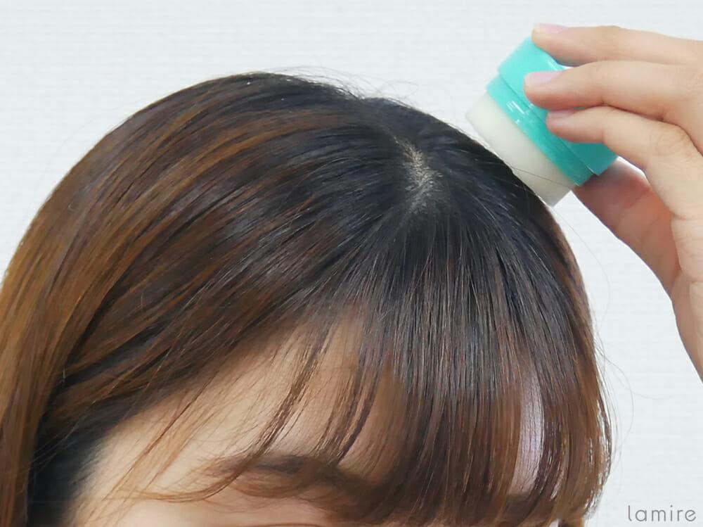 ウテナのまとめ髪スティックで浮き毛を直している女性の写真