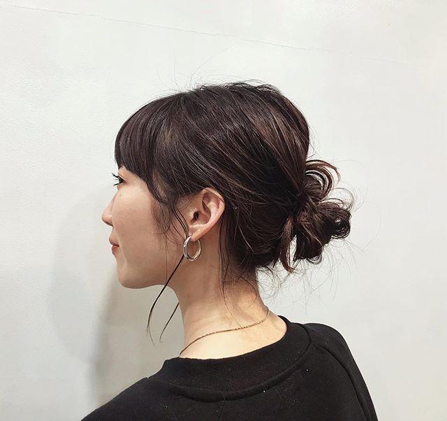 お団子にヘアアレンジしている直毛の黒髪ミディアムボブヘアスタイルの女性